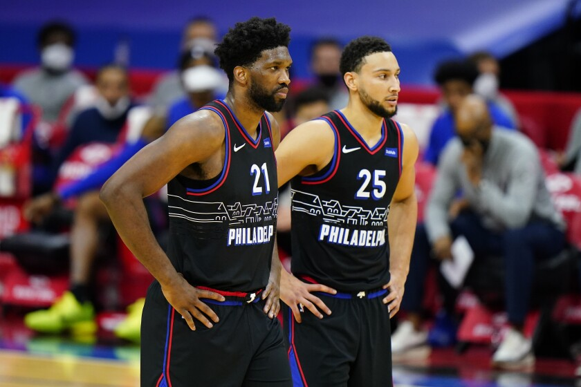 Joel Embiid and Ben Simmons stand side by side on court.