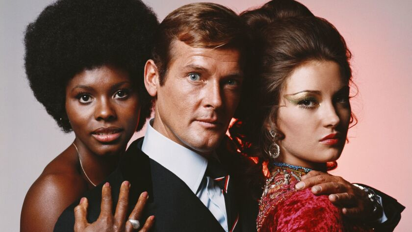 "English actor Roger Moore in his role as James Bond in Guy Hamilton's film ""Live and Let Die,"" circa 1973, with costars Gloria Hendry (left) and Jane Seymour."