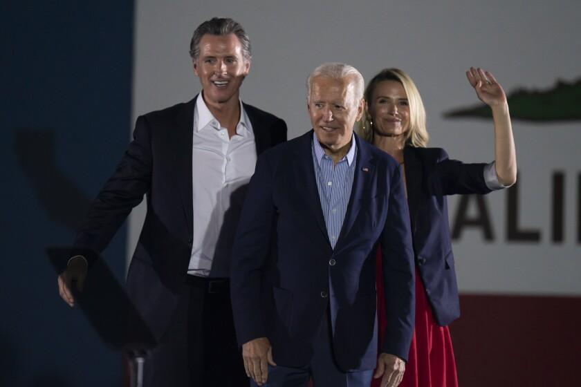 President Joe Biden, center, smiles to the crowd as he is flanked by California Gov. Gavin Newsom