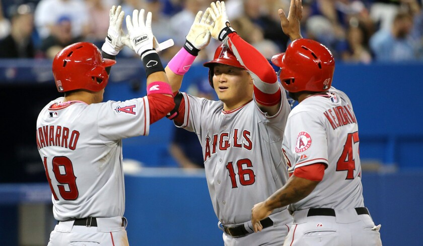 Angels catcher Hank Conger (16) celebrates with teammates Efren Navarro (19) and Howie Kendrick (47) after hitting a three-run home run against the Blue Jays in the sixth inning Sunday in Toronto.