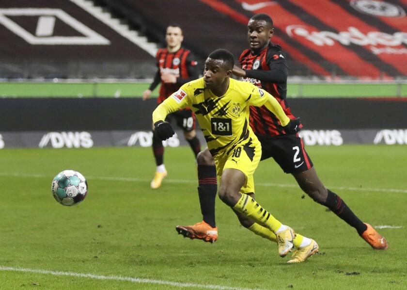 Evan N'Dicka, de Eintracht, derecha, y Youssoufa Moukoko