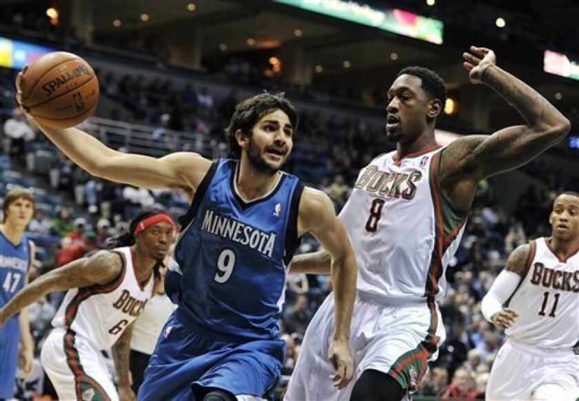 Minnesota Timberwolves' Ricky Rubio (9) drives past Milwaukee Bucks' Larry Sanders (8) during the first half of an NBA basketball game, Wednesday, April 3, 2013, in Milwaukee. (AP Photo/Jim Prisching)