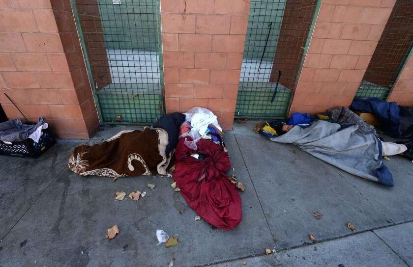 Homeless people sleep on skid row in Los Angeles.