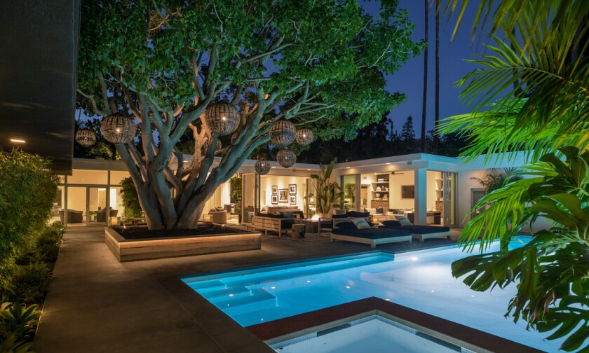 Built in 1959, the chic Midcentury expands to a resort-like backyard with lounges and a swimming pool.