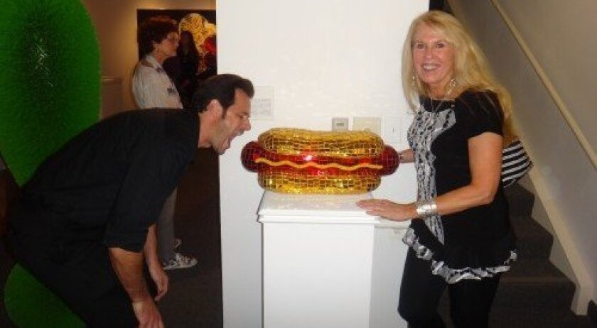 "Rancho Santa Fe artist Jean Wells' hot dog is currently on display in the Frederick R. Weisman Museum of Art's ""Pop Culture"" exhibit. She is seen here with fellow artist Robert Townsend pretending to take a bite."
