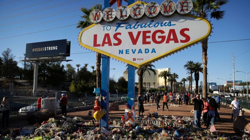 "Flowers, candles and other items surround the Las Vegas sign on Oct. 9 as a makeshift memorial for victims of a mass shooting earlier that month. The city has revived its famous slogan ""What happens here, stays here."""