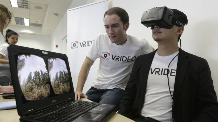 Vrideo co-founders Alex Rosenfeld, left, and Kuangwei Hwang with the Oculus VR viewer at a meet-up in Santa Monica in 2015. Vrideo ended up closing because it ran out of funding.
