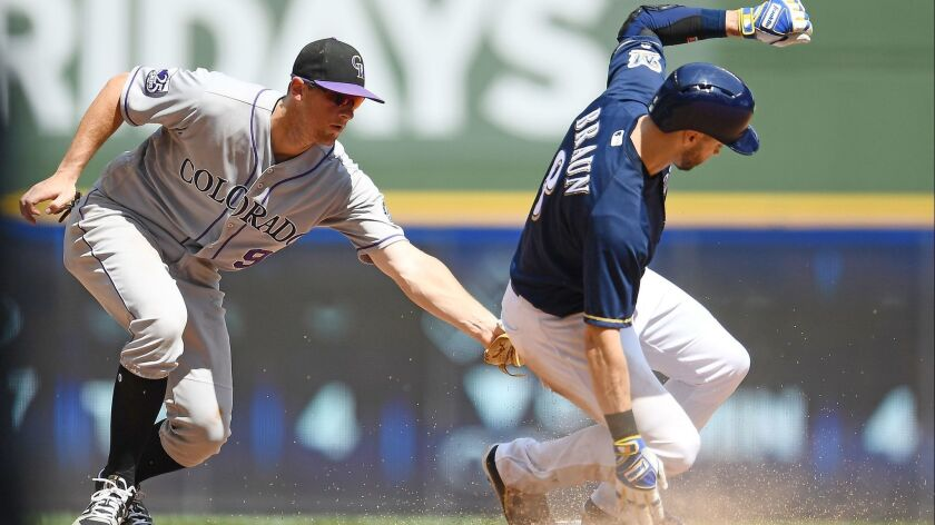 Ryan Braun of the Milwaukee Brewers beats a tag by D.J. LeMahieu of the Colorado Rockies to steal second base during the fifth inning of a game at Miller Park on August 5, 2018 in Milwaukee, Wisconsin.