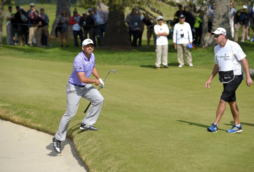 Sergio Garcia, of Spain, climbs out of a bunker on the 10th hole after hitting his ball back to the 13th fairway during the third round of the Northern Trust Open at Riviera Country Club on Saturday.