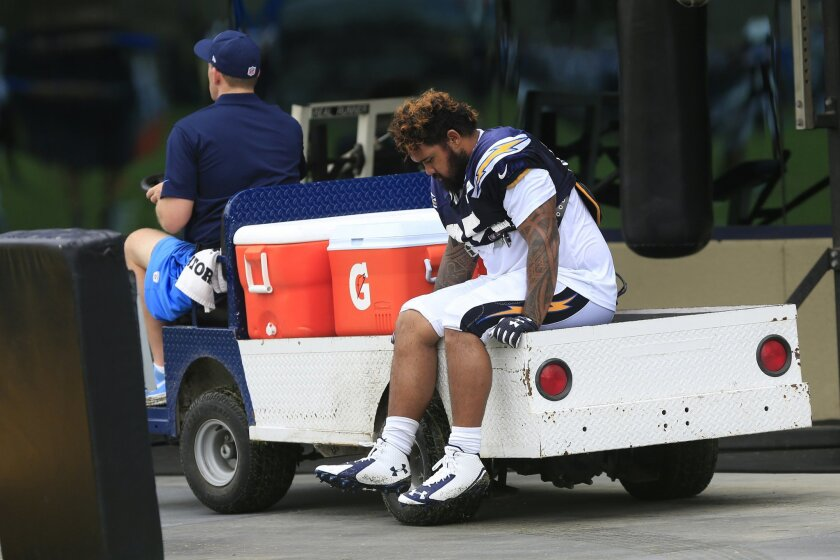 Chargers defensive tackle Tenny Palepoi is carted off the field after suffering a foot injury during practice at Chargers Park on the first day wearing full pads.