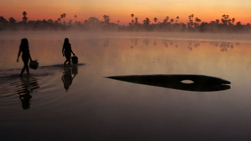 Indigenous women collect water from the lake Ipatse the morning after the first day of the Kuarup fe