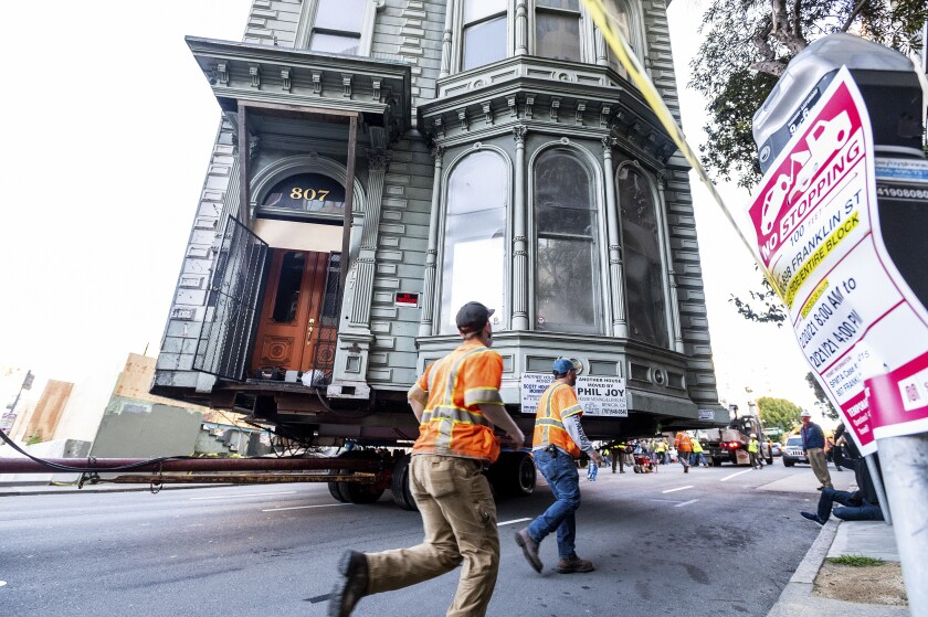 Workers pass a Victorian home as a truck pulls it along a San Francisco street.