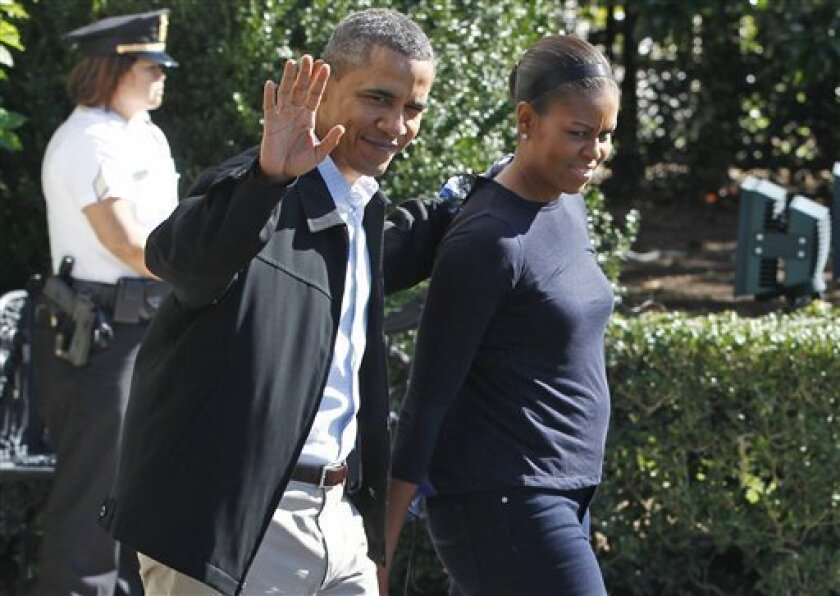 President Barack Obama and first lady Michelle Obama walk on the South Lawn of the White House in Washington as they leave for the presidential retreat at Camp David, Saturday, Oct. 2, 2010. (AP Photo/Charles Dharapak)