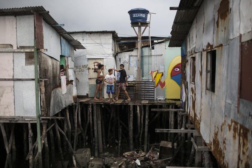 En esta imagen, Tainara Lourenco, quien tiene cinco meses de embarazo, sale de su casa construida sobre aguas contaminadas en una favela de Recife, Brasil. Lourenco se embarazó en un momento delicado, el extraordinario brote de virus zika, del que las autoridades sospechan que ha provocado un alarmante incremento en un raro defecto de nacimiento conocido como microcefalia. (Foto AP/Felipe Dana)