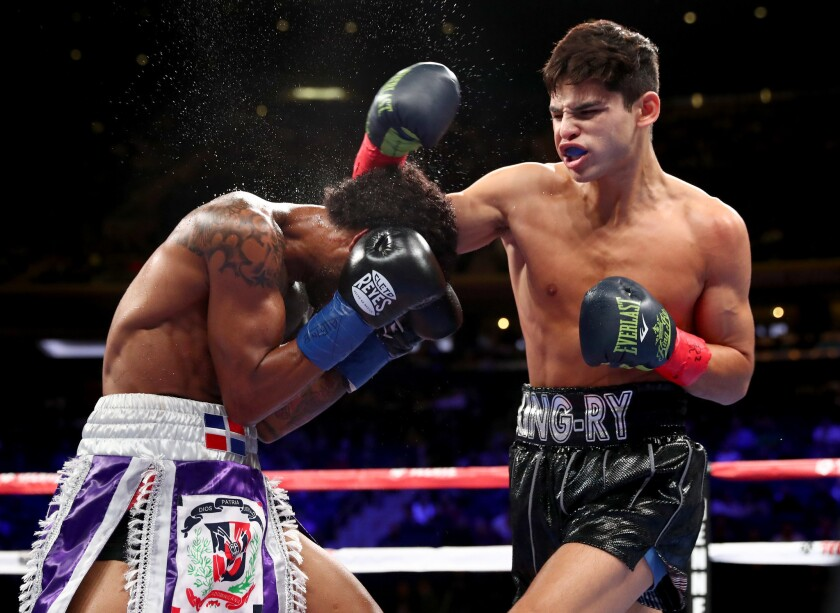 Ryan Garcia, right, lands a punch in the boxing ring against Braulio Rodriguez