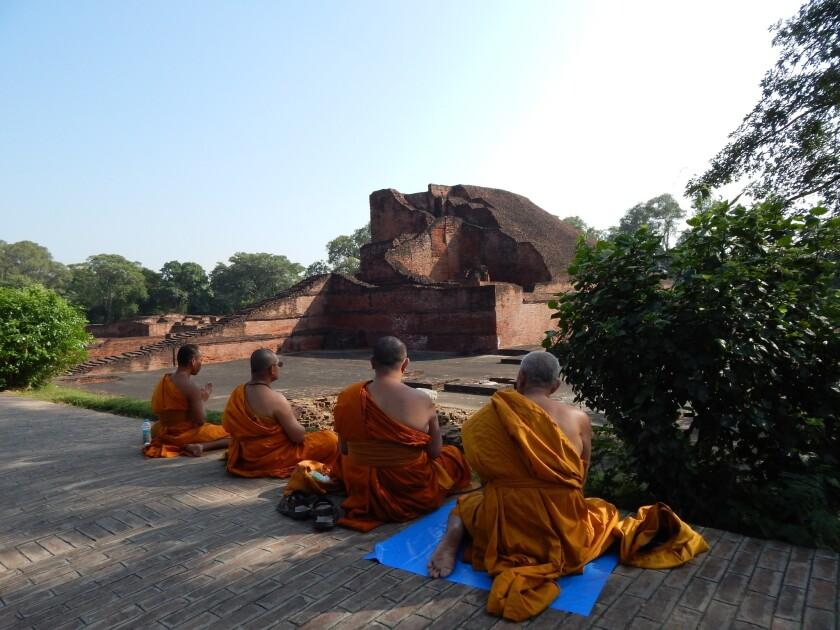 Buddhists praying at Nalanda University archaeological site.