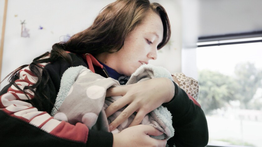 "(L-R)- Raeanne holding her baby in a scene from the HBO documentary ""Foster."" Credit: HBO"