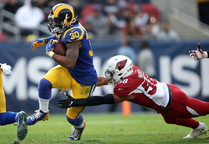 Rams running back Todd Gurley breaks the tackle of Arizona Cardinals defender Jordan Hicks during the first half at the Coliseum on Dec. 29, 2019.