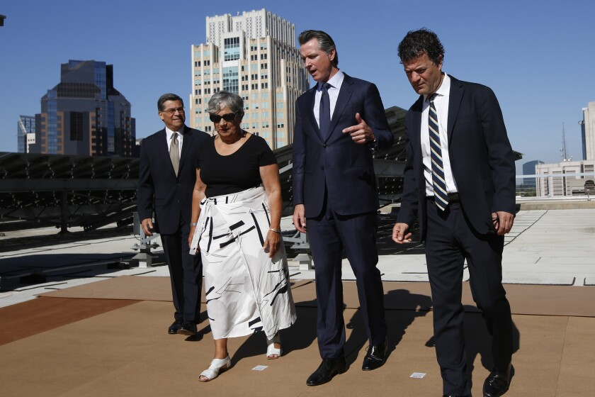 Calif Gov. Gavin Newsom, second from right, tours the solar panels atop the building housing the California Environmental Protection Agency accompanied by Attorney General Xavier Becerra, left, California Air Resources Board Chairwoman Mary Nichols, and California EPA Director Jared Blumenfeld, right in Sacramento, Calif., Tuesday, Aug. 13, 2019. California is part of coalition of 22 Democrat-led states that is suing the Trump administration over its decision to ease restrictions on coal-fired power plants. (AP Photo/Rich Pedroncelli)