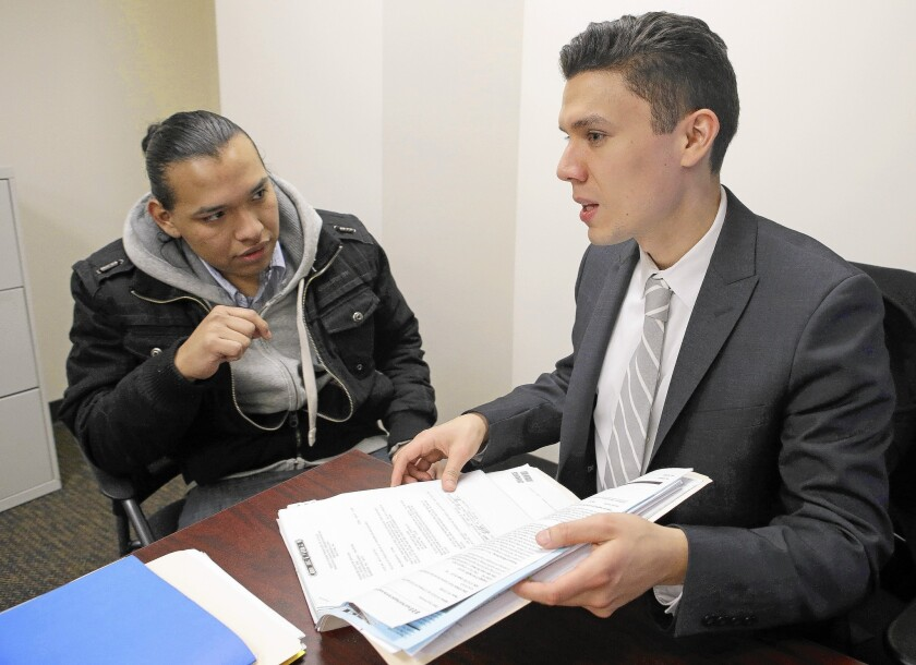 Oscar Hernandez, left, meets with attorney Ruben Loyo at Brooklyn Defender Services in New York. Hernandez, 20, is being helped by a pilot program in the city that provides free legal aid for low-income immigrants who face deportation.