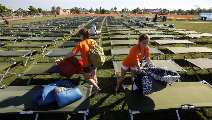 In this photo from last year's event, El Cajon Valley High School students Morgaine Judkins, left, and Ashlee Peterson, set up cots for  Sleepless San Diego. The annual event is aimed at giving participants a fresh perspective on homelessness, and is scheduled for Saturday in Liberty Station.