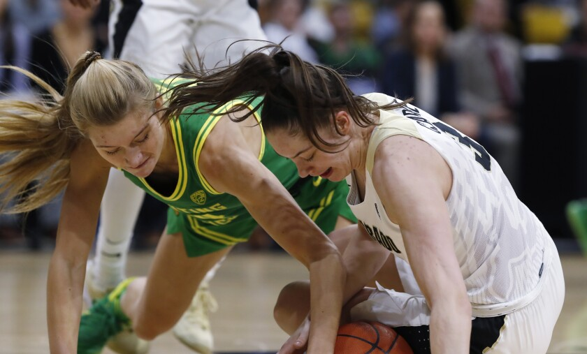 Oregon forward Lydia Giomi, left, fights for control of a loose ball with Colorado guard Emma Clarke in the first half of an NCAA college basketball game Saturday, Feb. 1, 2020, in Boulder, Colo. (AP Photo/David Zalubowski)