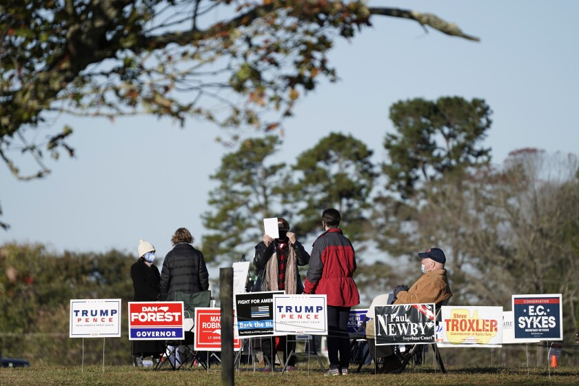 Polling workers assist voters on a brisk fall morning at the Efland Ruritan Club polling site in Efland, N.C., Tuesday, Nov. 3, 2020. (AP Photo/Gerry Broome)