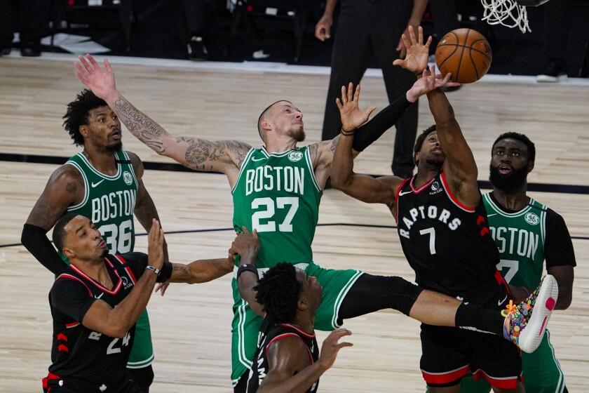 Boston Celtics center Daniel Theis tries to shoot over Toronto Raptors guard Kyle Lowry.