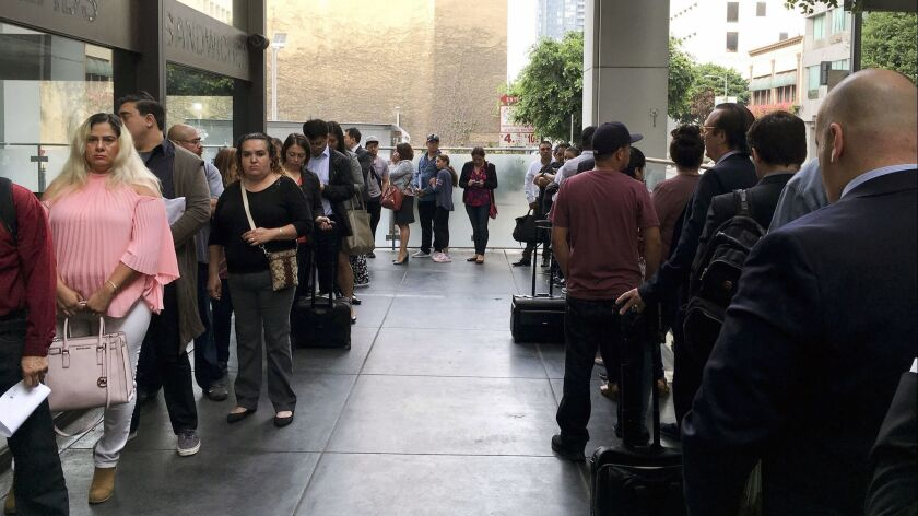 Immigrants awaiting deportation hearings line up outside the building that houses the immigration courts in Los Angeles on June 19.