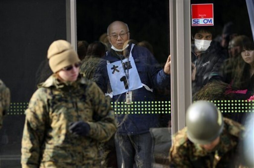 FILE - In this March 26, 2011 file photo, curious local residents at a shelter watch U.S. Marines install hot showers in Higashi Matsushima as the U.S. military has been quick to respond to the tsunami that devastated northeastern Japan. Japanese have become more welcoming to the U.S. military presence in their country over the past six years as fears spread that neighboring China and North Korea are threats to peace, an Associated Press-GfK poll released Monday, Sept. 5, 2011 has found. (AP Photo/Wally Santana, File)