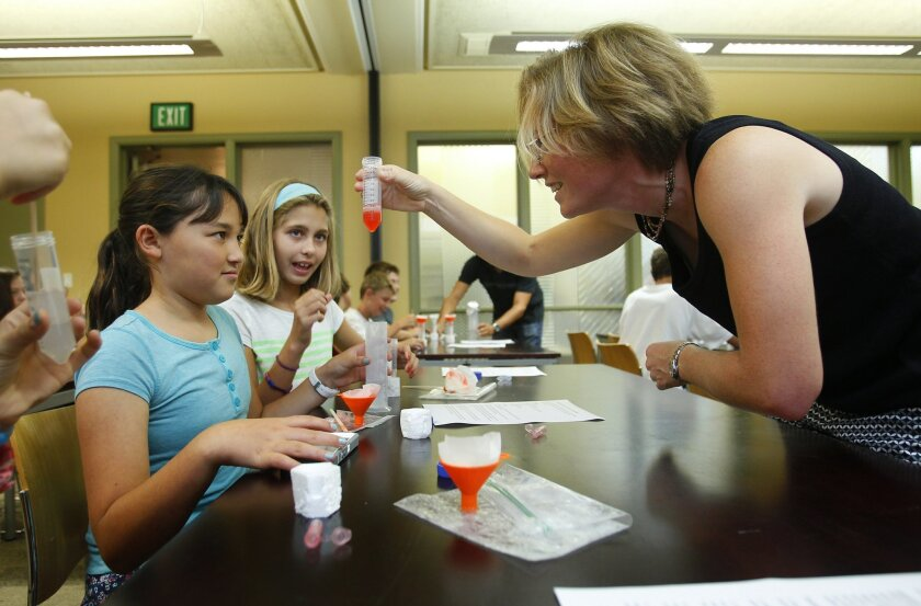 Muirlands Middle School students Lauren Nitahara, left, and Monica O'Brien precipitate DNA from a strawberry with Dr. Callen Hyland, a volunteer at the new public biotech lab at the La Jolla-Riford Library.