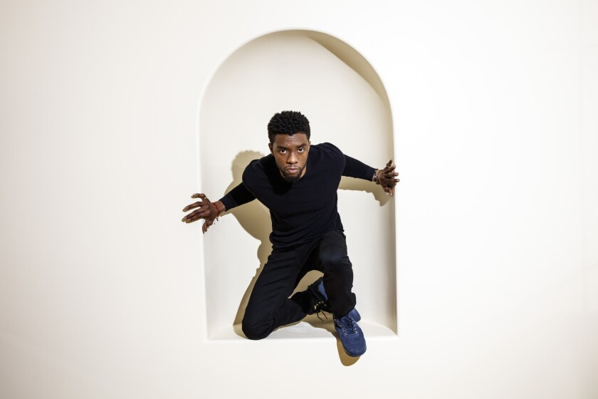 Late actor Chadwick Boseman crouches in the arch of a wall inset
