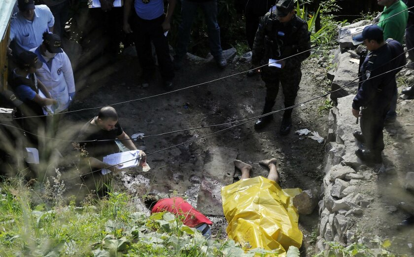 Crime scene investigators gather evidence around the body of a man that was killed when armed young men pulled several men from their homes and executed them, at a low income neighborhood in the capital city of Tegucigalpa, Honduras, Wednesday, Nov. 25, 2015. Honduran police say more than a dozen people have died in two massacres within a span of 12 hours. Another eight were killed in the city of San Pedro Sula after armed men stormed a bus terminal and shot eight drivers one by one. It was a bloody 12 hours for Honduras, which only recently was designated the world's deadliest country for a nation not at war. (AP Photo/Fernando Antonio)