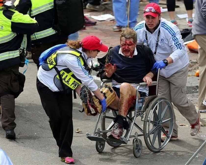 Medical workers aid an injured man at the 2013 Boston Marathon following an explosion in Boston, Monday, April 15, 2013. Two bombs exploded near the finish of the Boston Marathon on Monday, killing at least two people, injuring at least 22 others and sending authorities rushing to aid wounded spect
