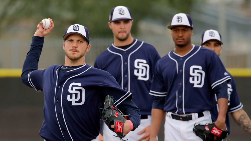 San Diego Padres pitchers watch Paul Clemens throw during a drill at spring training baseball practice Friday, Feb. 17, 2017, in Peoria, Ariz. (AP Photo/Charlie Riedel)