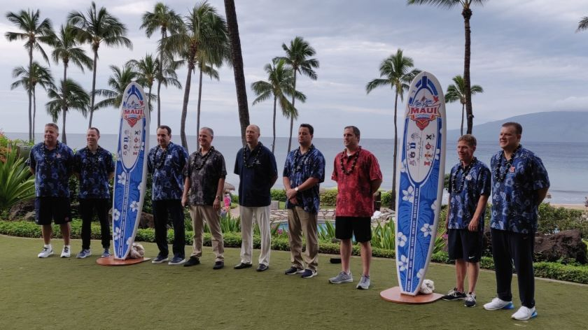 Coaches at the 2018 Maui Invitational basketball tournament pose for a photo with surfboards.