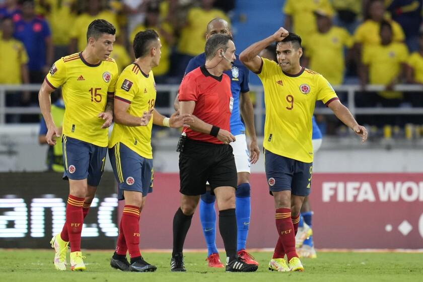 Los jugadores de Colombia rodean al árbitro Patricio Loustau al reclamar un penal en el partido