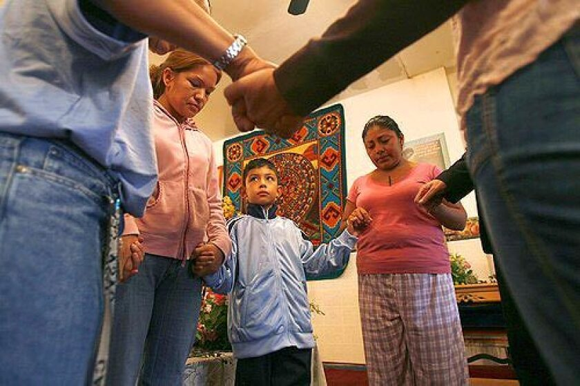 """PRAYER: Elvira Arellano, left, and son Saul at Adalberto United Methodist Church in Chicago. A growing """"sanctuary"""" movement seeking to protect illegal immigrants from deportation is working to keep Arellano and Saul from being separated. Saul has traveled the U.S. to draw attention to their case and millions of others."""