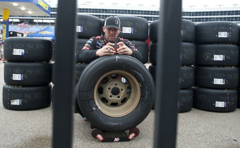 Dustin Keath checks tires for Sprint Cup Series driver Greg Biffle during a NASCAR auto race weather delay at Texas Motor Speedway Saturday, Nov. 7, 2015, in Fort Worth, Texas. The morning and afternoon practice session were canceled. (AP Photo/Ralph Lauer)