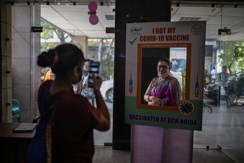 Una mujer posa para una foto en un marco de cartón indicando que se ha vacunado del COVID-19, en un hospital de Noida, un suburbio de Nueva Delhi, India, el miércoles 7 de abril de 2021. (AP Foto/Altaf Qadri)