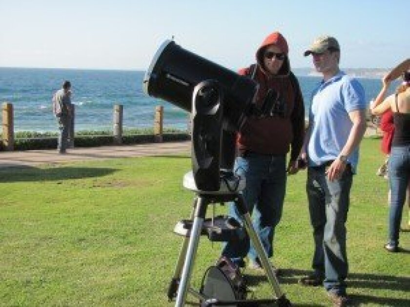 Matt Mofidi (right) explains to a beach-goer why his telescope is aimed at the sun, June 5.