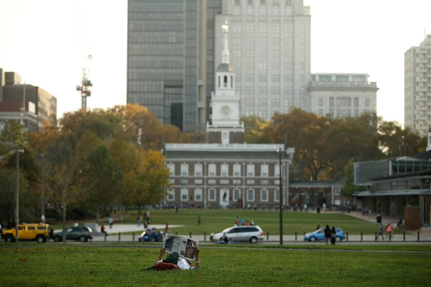 A man reads a newspaper near Independence Hall, Friday, Nov. 6, 2015, in Philadelphia. America's birthplace has been named the country's first World Heritage City. The Organization of World Heritage Cities voted in Peru on Friday to add Philadelphia. The city qualifies because Independence Hall is