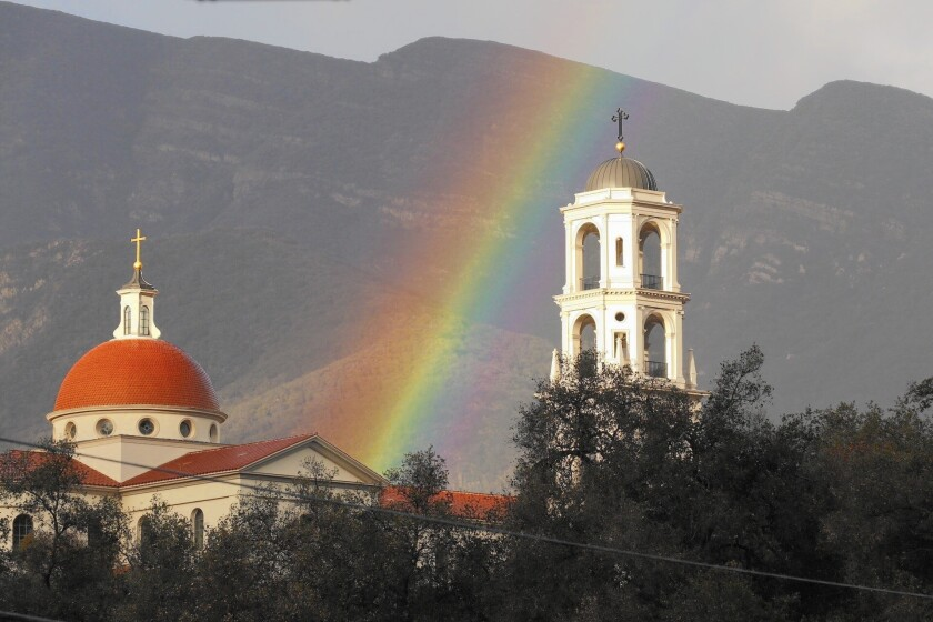 A rainbow appears to rise above Thomas Aquinas College in Santa Paula. Another storm system is forecast to hit Southern California on Saturday.