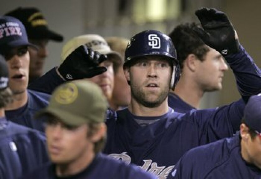 Kevin Kouzmanoff gets high fives in the dugout after his 2-out home run against the Angels' Joe Saunders in the first inning, providing the Padres' first offense. Photo by Charlie Neuman/San Diego Union-Tribune