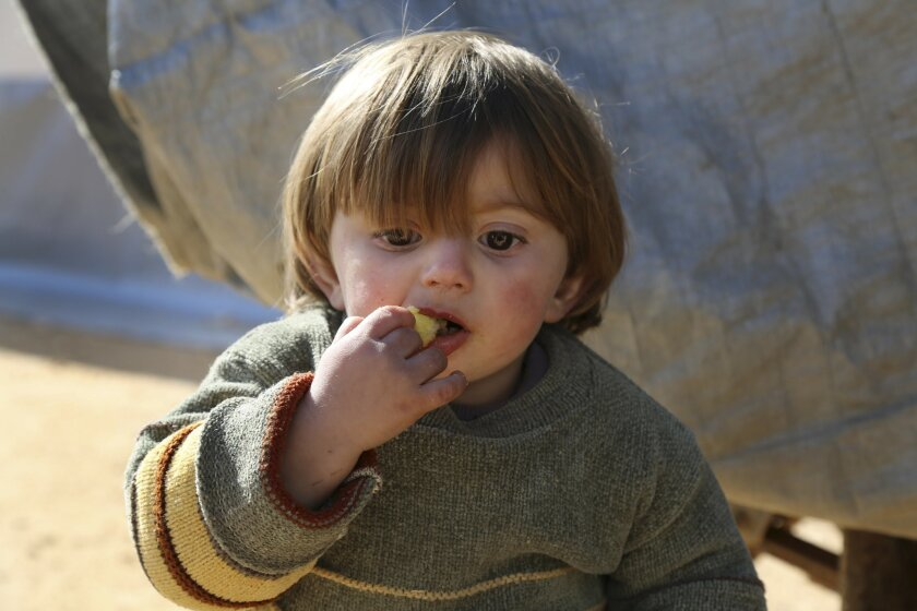 In this photo provided by Turkish Islamic aid group IHH, a displaced Syrian boy eats at a temporary refugee camp in northern Syria, near Bab al-Salameh border crossing with Turkey, Monday, Feb. 8, 2016. Turkey was under pressure from the EU to open its border to up to 35,000 Syrians who have massed