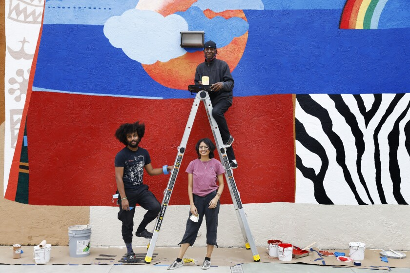 Two people below a ladder and one person on it in front of a mural