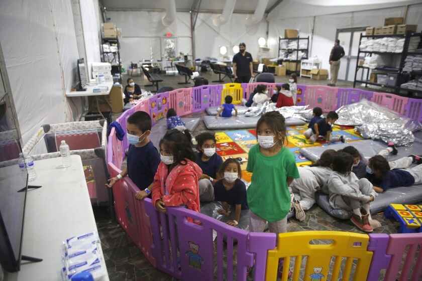Children watch television inside a playpen at the U.S. Customs and Border Protection facility.