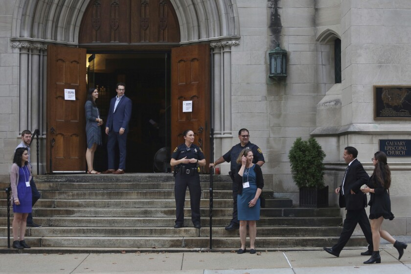 FILE - In this Sunday, Sept. 29, 2019 file photo, members of the Jewish community arrive for services as Pittsburgh Police Detectives provide security on the first night of Rosh Hashana at Calvary Episcopal Church in Pittsburgh. The church offered Tree of Life congregants to hold services there to accommodate the expected larger number of congregants attending Rosh Hashana services this year. The Tree of Life congregation has been worshipping at alternate sites since a gunman killed 11 people at their synagogue on Oct. 27, 2018. (Rebecca Droke via AP)