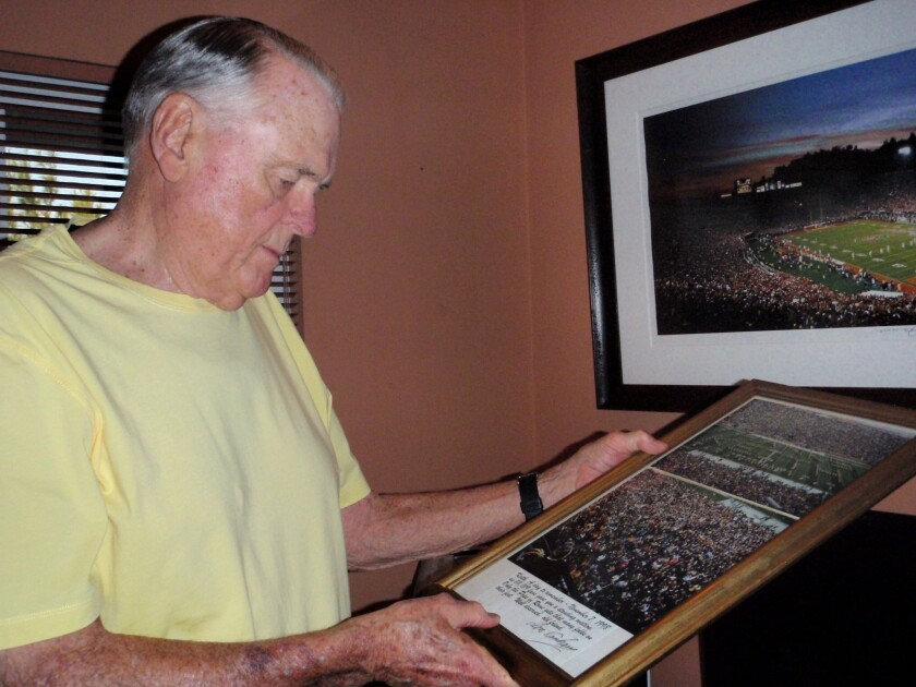 """Former ABC Sports college football broadcaster Keith Jackson holds a photo of the Michigan band spelling out """"Thanks Keith"""" during a farewell halftime show. Jackson says current sports broadcasters talk too much."""