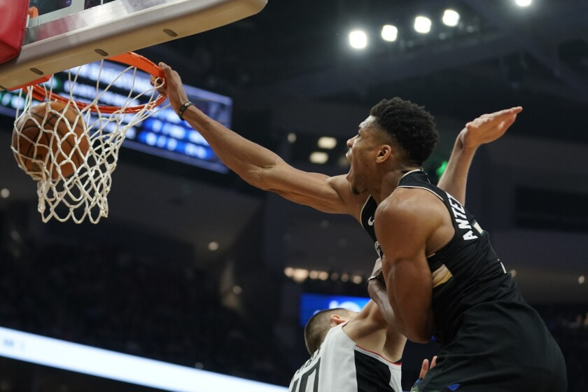 The Bucks' Giannis Antetokounmpo dunks on the Clippers' Ivica Zubac during the second half.